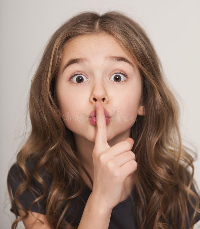 Menina bonita com o dedo nos bordos f fotos de stock royalty free