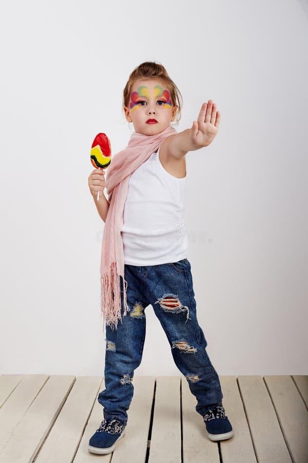 A menina bonita com o pirulito com mão pintada da parada da exibição da cara nas crianças ama o conceito do doce e do açúcar fotografia de stock