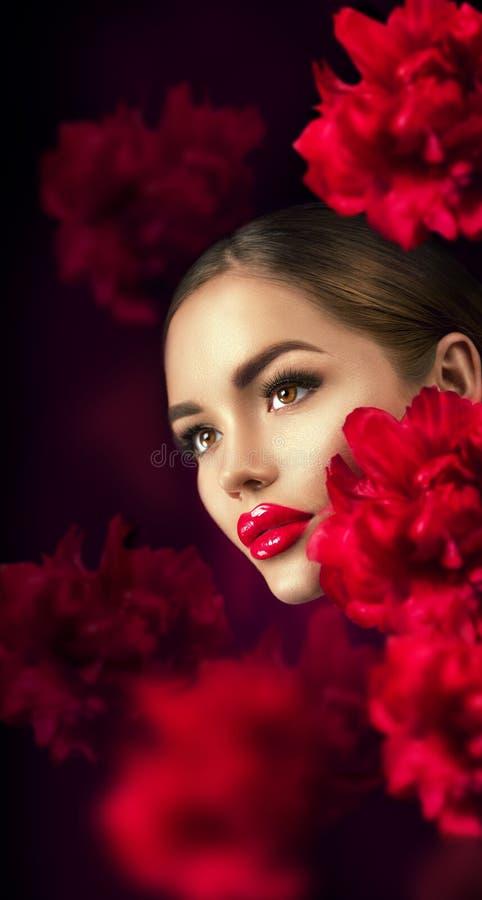 Menina bonita com o retrato vermelho das flores da peônia Cara da mulher do modelo de forma da beleza fotos de stock