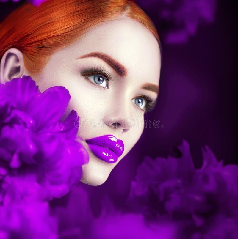 Menina bonita com o retrato violeta das flores da peônia Cara modelo da mulher do ruivo da forma da beleza foto de stock