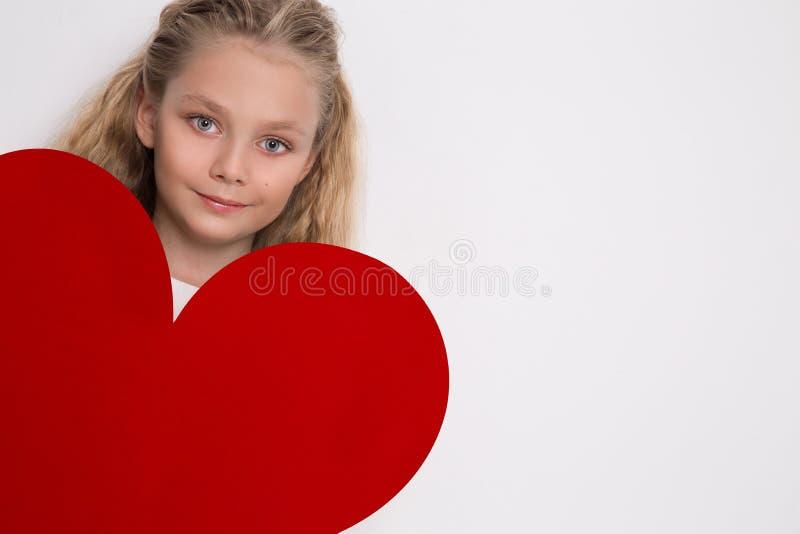 A menina bonita com olhos azuis surpreendentes e cabelo louro longo realiza em seu coração do vermelho do Valentim das mãos fotografia de stock