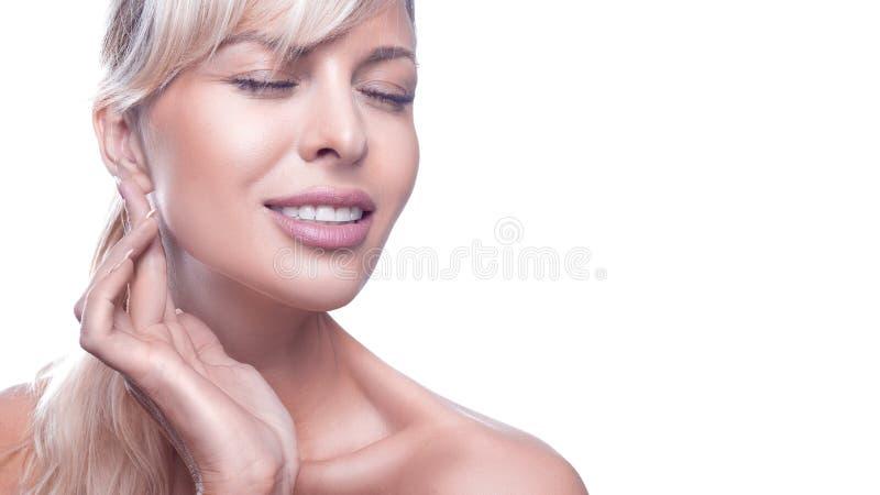 Menina bonita com olhos fechados e a pele limpa isolados no fundo branco Mulher que toca na pele macia de sua cara fotos de stock royalty free