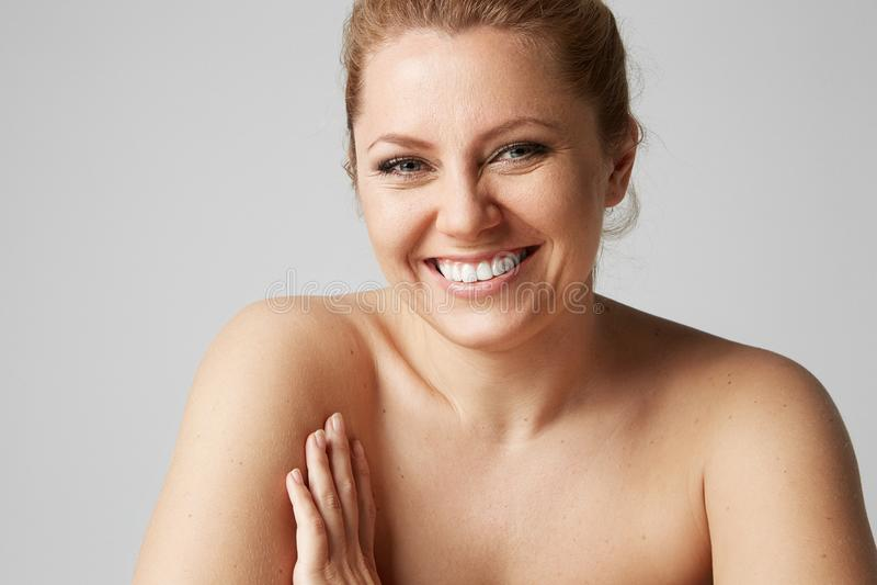 Menina bonita com olhos grandes e as sobrancelhas escuras, com os ombros despidos, olhando a câmera e o sorriso Modelo com nude c foto de stock