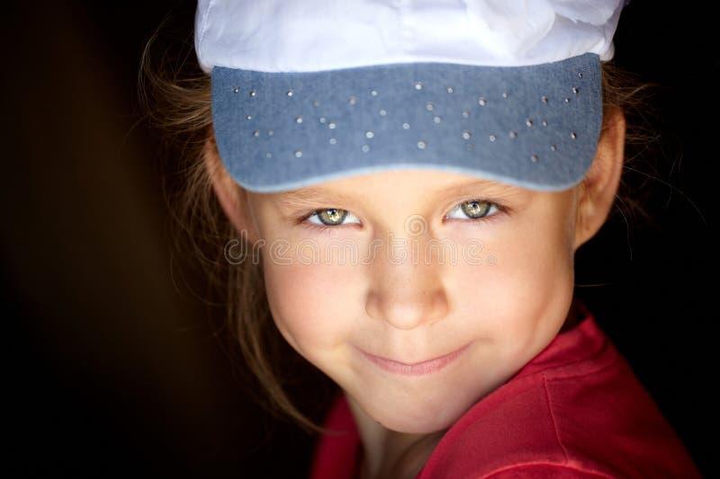 Menina bonita com olhos verdes em um tampão branco e vista imagem de stock