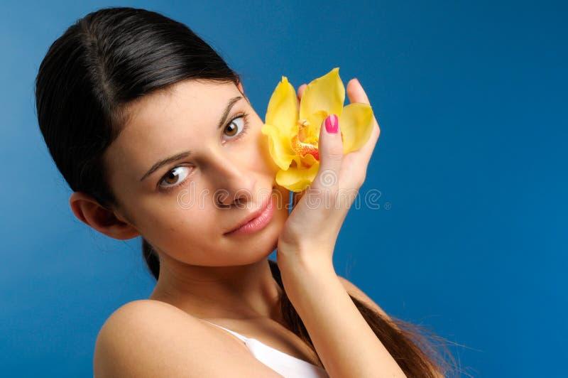 Menina bonita com orquídea amarela imagem de stock royalty free