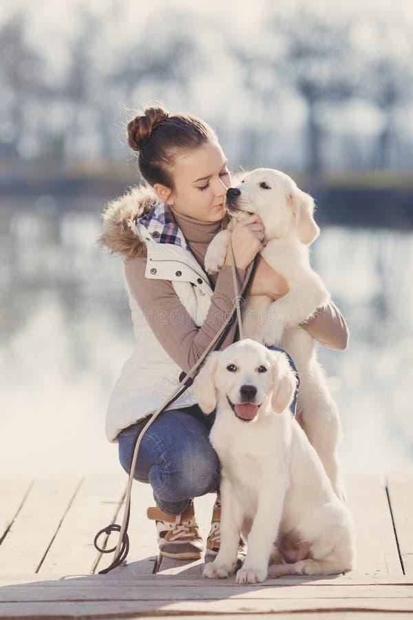 Menina bonita com os animais de estimação perto do lago imagens de stock royalty free
