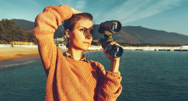Menina bonita com os binóculos à disposição que estão pelo mar e pelo E foto de stock