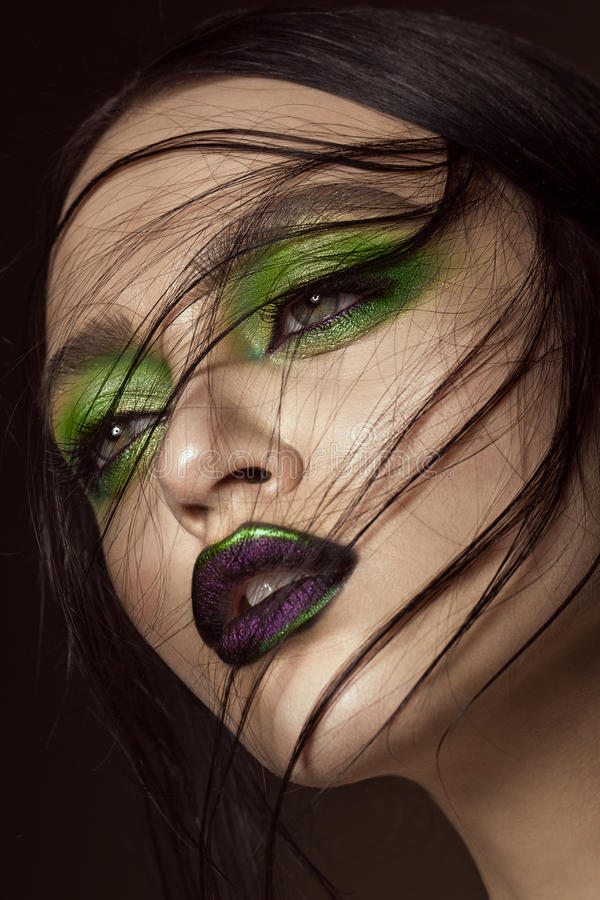 Menina bonita com os bordos da composição e do vampiro do verde da mola Face da beleza imagem de stock royalty free