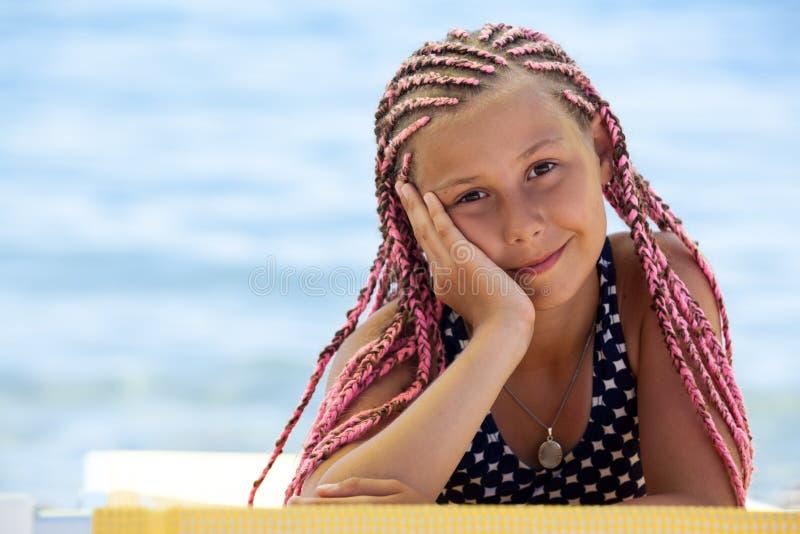 Menina bonita com os dreadlocks africanos cor-de-rosa que encontram-se no vadio amarelo do sol, olhando a c?mera com sorriso, esp imagens de stock