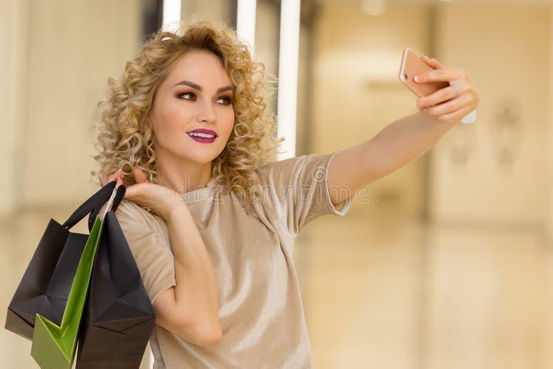 Menina bonita com os sacos de compras que tomam um selfie com seu telefone celular fotografia de stock royalty free