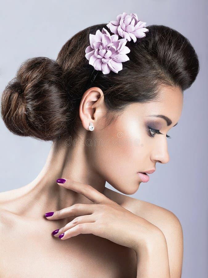 A menina bonita com pele perfeita e roxo floresce em sua cabeça fotos de stock royalty free