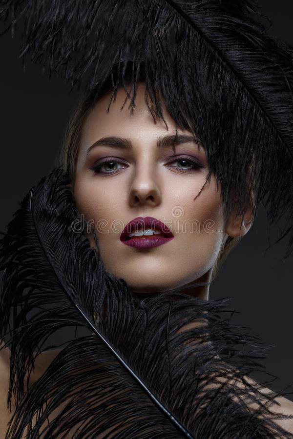Menina bonita com penas pretas imagens de stock