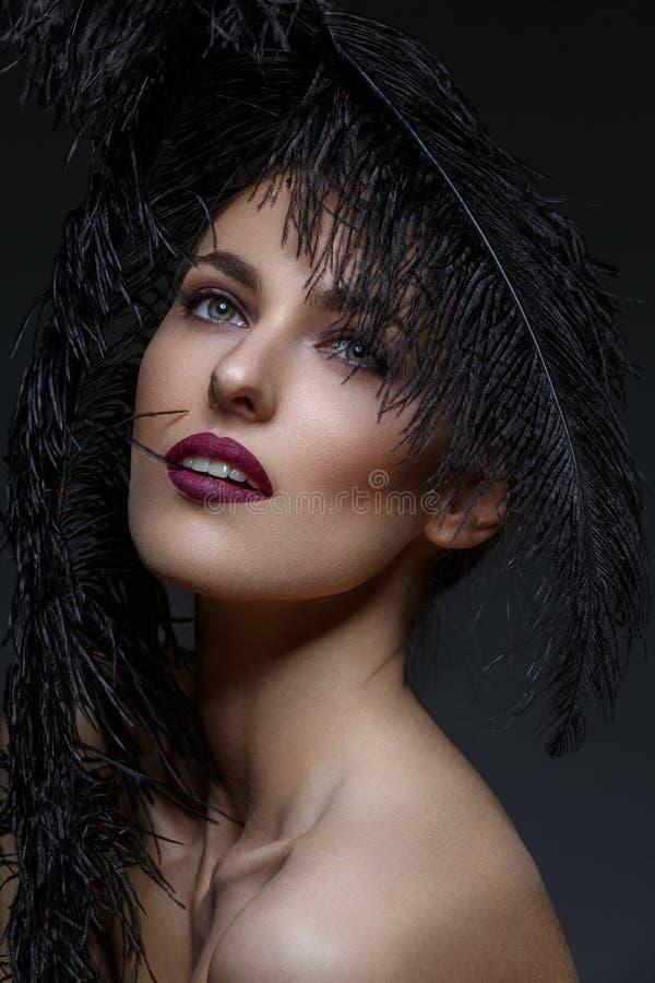 Menina bonita com penas pretas imagem de stock royalty free