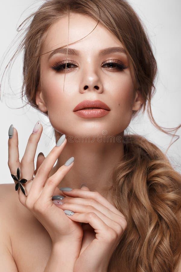 Menina bonita com penteado fácil, composição clássica, os bordos nude e o projeto do tratamento de mãos Face da beleza Pregos da  foto de stock royalty free
