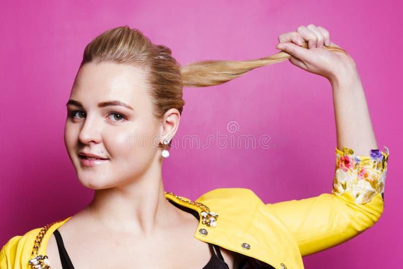 A menina bonita com perfuração e brincos mostra-lhe o cabelo foto de stock royalty free