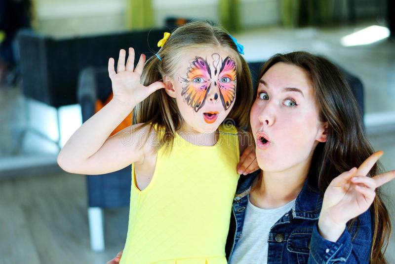 Menina bonita com pintura da cara de uma borboleta com baby-sitter fotografia de stock