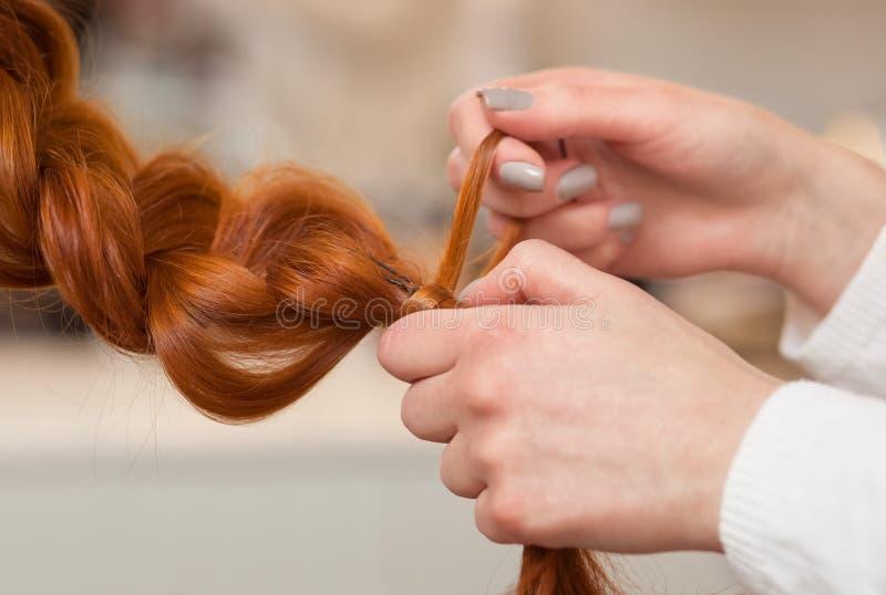 A menina bonita com por muito tempo, vermelho-cabelo, cabeleireiro tece um close-up da trança, em um salão de beleza imagem de stock