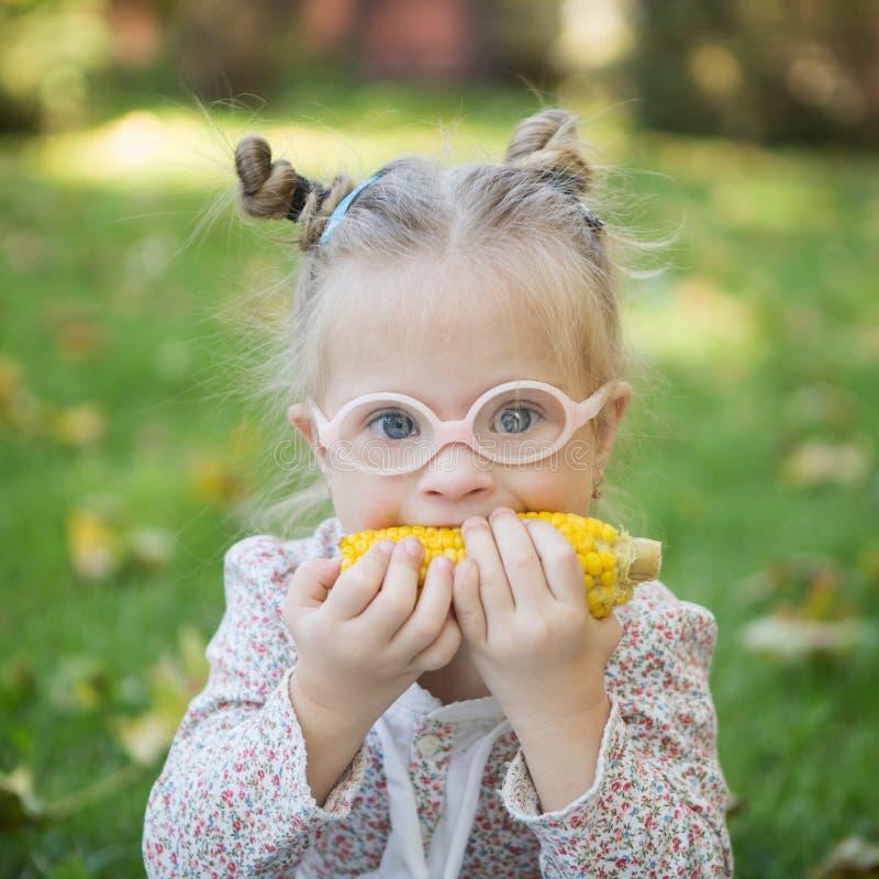 Menina bonita com Síndrome de Down que come o milho na natureza foto de stock royalty free
