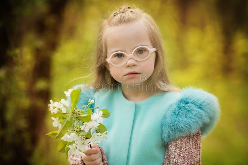 Menina bonita com a Síndrome de Down que guarda flores da mola imagem de stock