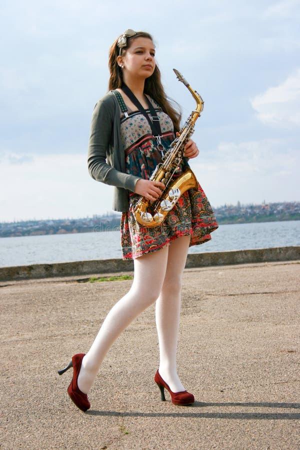 Menina bonita com saxofone foto de stock royalty free