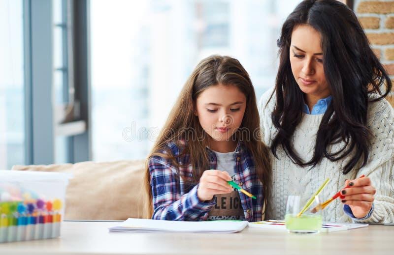 A menina bonita com sua pintura da mãe representa em casa foto de stock