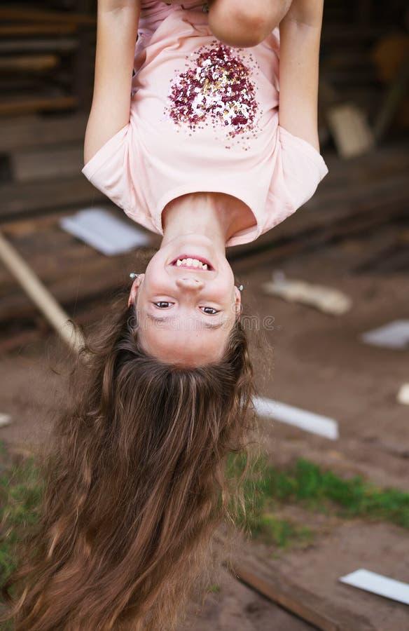 Menina bonita com a suspensão longa do cabelo de cabeça para baixo e o SMI foto de stock royalty free