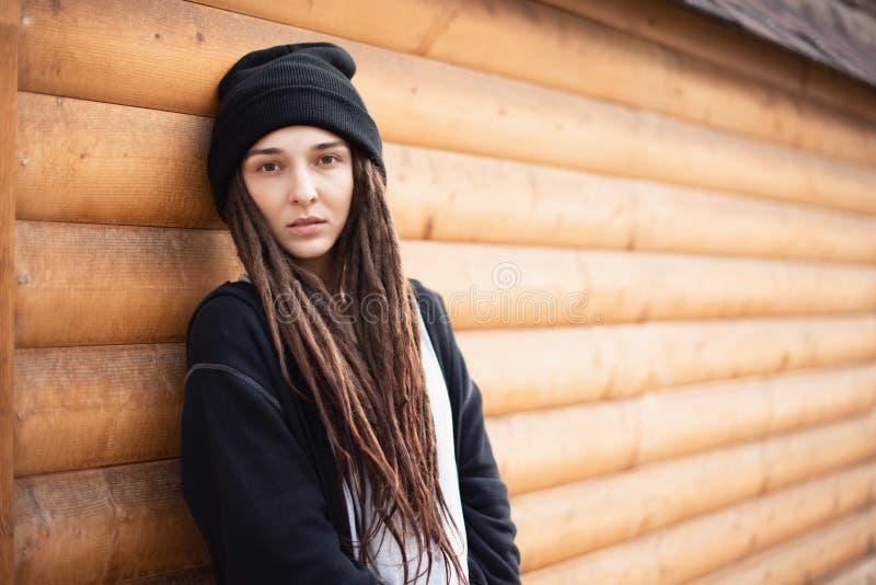 A menina bonita com teme em um chapéu negro em um fundo de uma casa de madeira imagens de stock royalty free