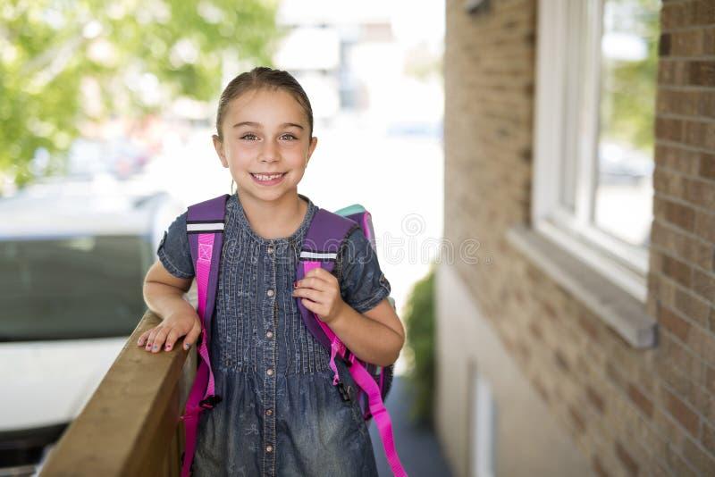 Menina bonita com a trouxa pronta de volta à escola foto de stock