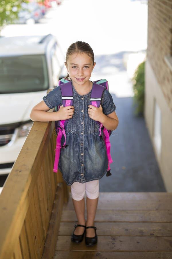 Menina bonita com a trouxa pronta de volta à escola imagem de stock