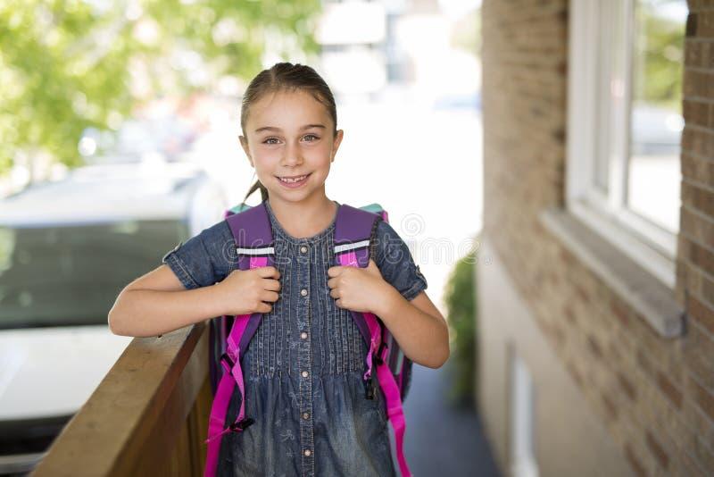 Menina bonita com a trouxa pronta de volta à escola fotografia de stock royalty free