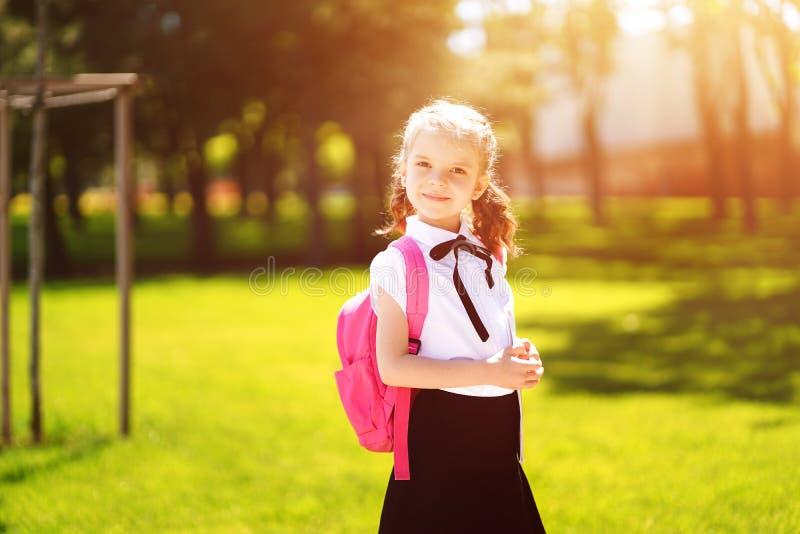 A menina bonita com trouxa que anda no parque pronto de volta ? escola, cai fora, conceito da educa??o foto de stock