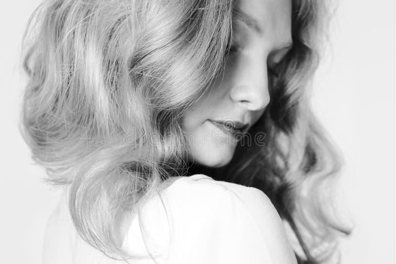 A menina bonita com um cabelo justo por sua vez friccionará imagem de stock