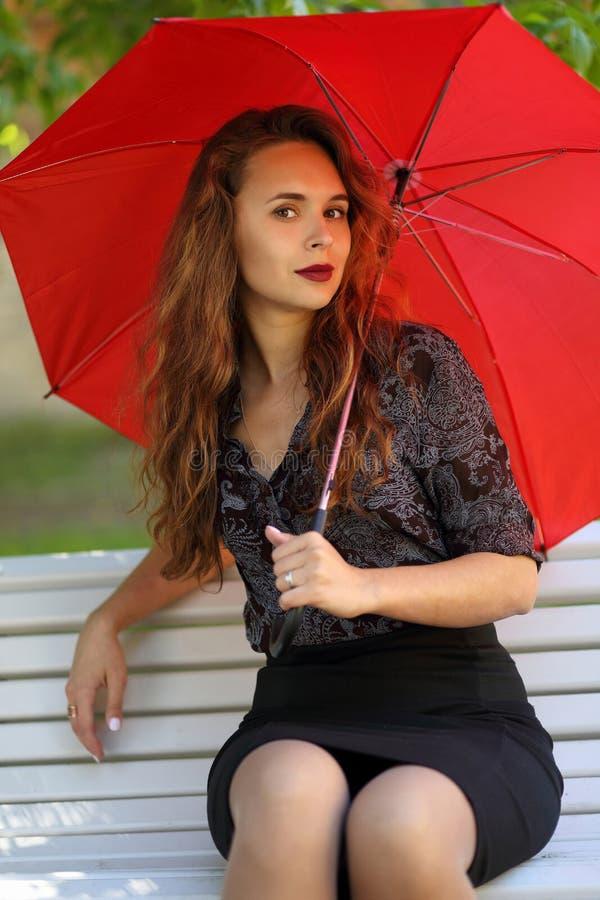 Menina bonita com um guarda-chuva vermelho em um banco de parque fotos de stock