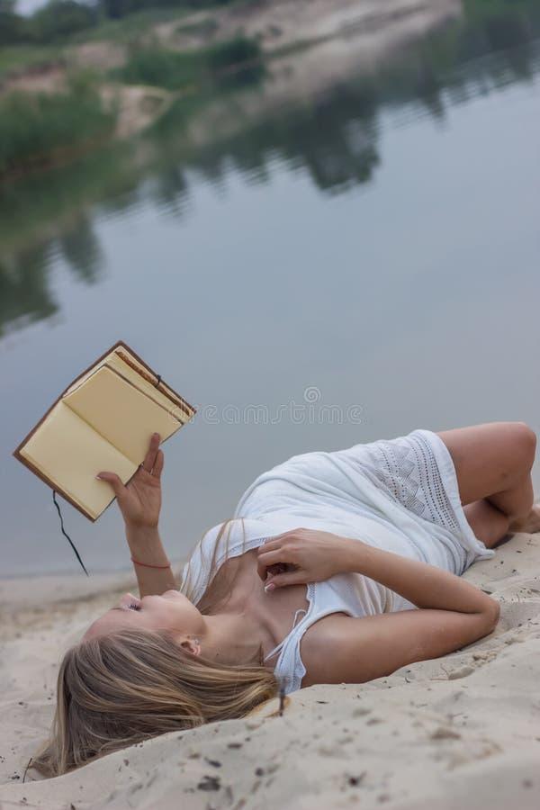 Menina bonita com um livro imagem de stock