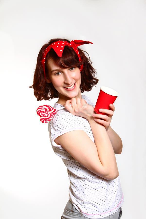 Menina bonita com um pirulito e um copo em uma parte traseira do cinza foto de stock royalty free