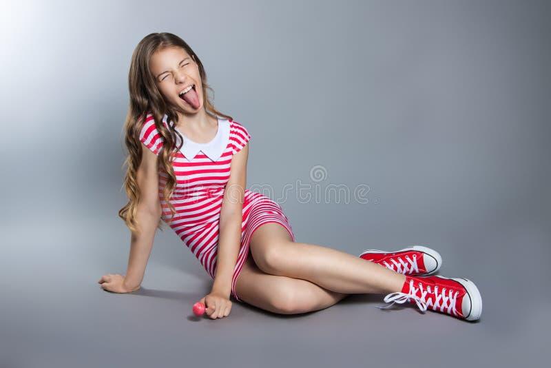 A menina bonita com um pirulito em sua mão está levantando em um fundo cinzento menina em um vestido no vermelho com listras bran fotografia de stock