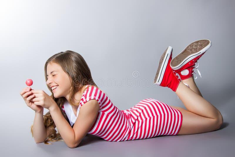 A menina bonita com um pirulito em sua mão está levantando em um fundo cinzento menina em um vestido no vermelho com listras bran imagens de stock royalty free