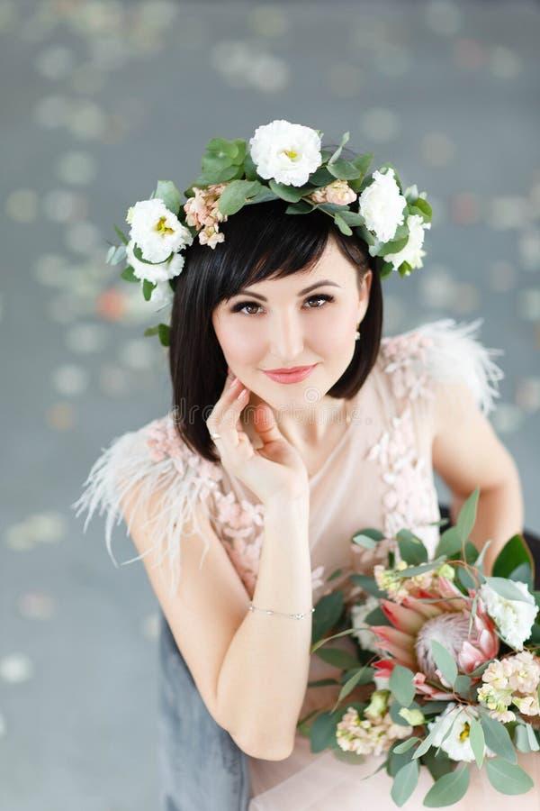 Menina bonita com um ramalhete ? disposi??o e uma grinalda das flores em sua cabe?a fotos de stock