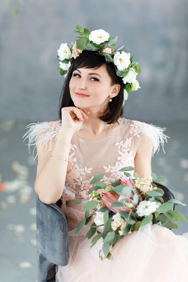 Menina bonita com um ramalhete ? disposi??o e uma grinalda das flores em sua cabe?a imagens de stock royalty free