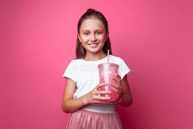 Menina bonita com uma bebida ou cocktail em suas mãos, em um fundo cor-de-rosa, em um estúdio da foto, close-up fotografia de stock