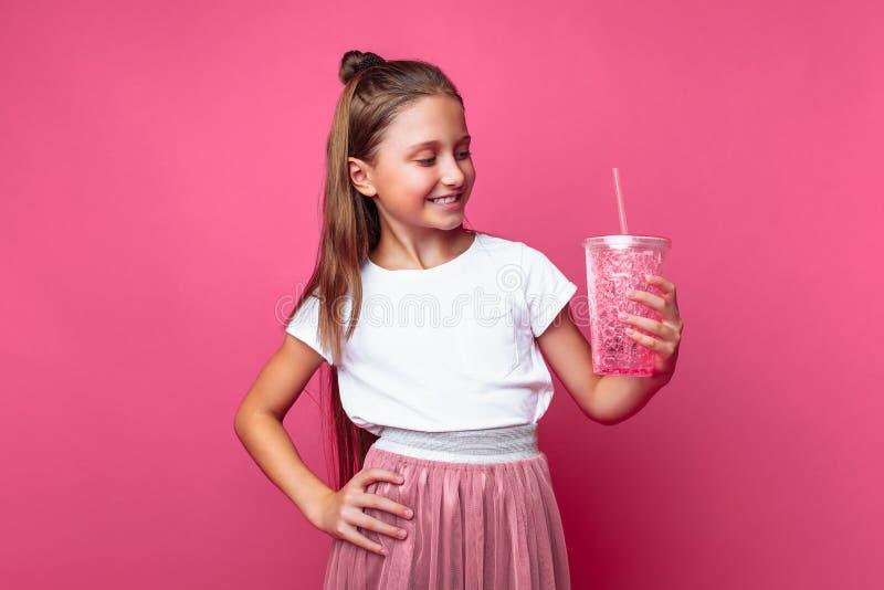 Menina bonita com uma bebida ou cocktail em suas mãos, em um fundo cor-de-rosa, em um estúdio da foto, close-up imagem de stock
