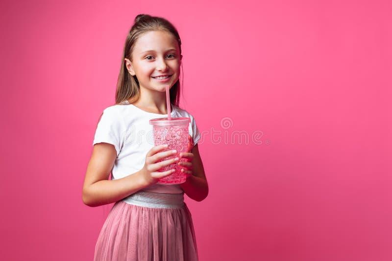 Menina bonita com uma bebida ou cocktail em suas mãos, em um fundo cor-de-rosa, em um estúdio da foto, close-up imagens de stock