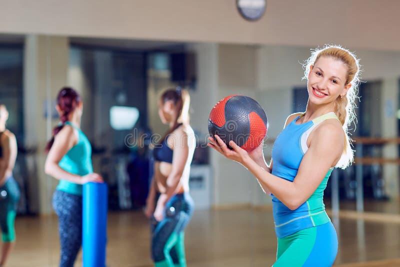 Menina bonita com uma bola em seus braços no gym imagens de stock