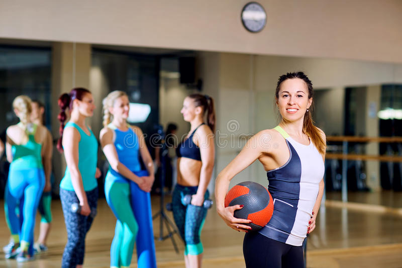 Menina bonita com uma bola em seus braços no gym imagens de stock royalty free