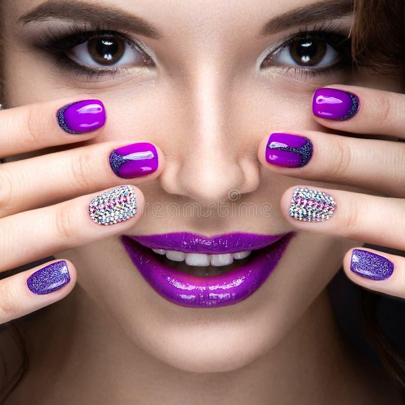 Menina bonita com uma composição brilhante da noite e tratamento de mãos roxo com cristais de rocha Projeto do prego Face da bele fotos de stock