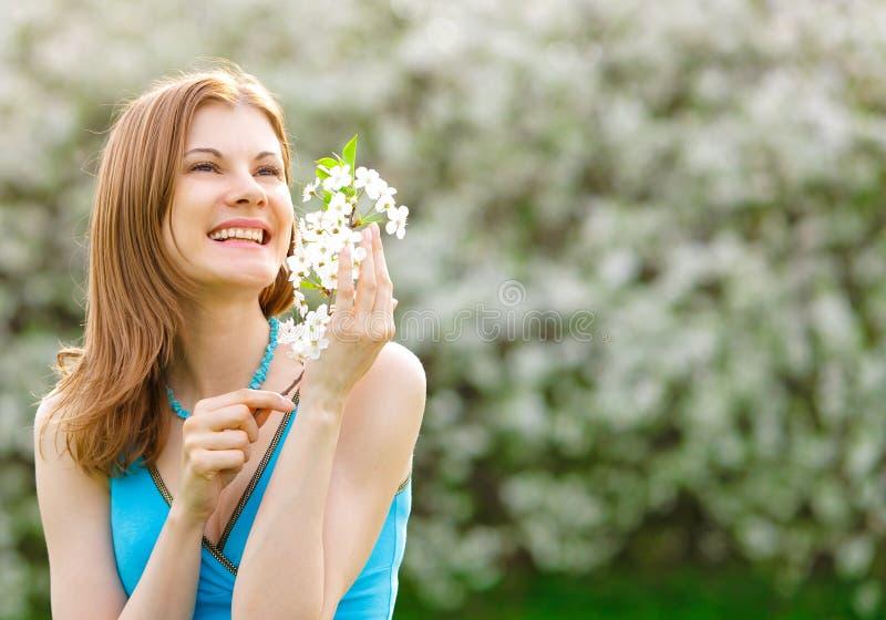 Menina bonita com uma flor ao ar livre imagem de stock