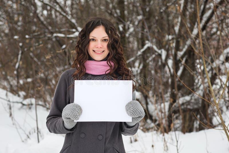 Menina bonita com uma folha de papel em branco foto de stock