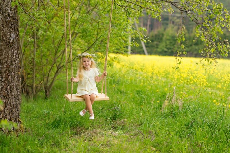 Menina bonita com uma grinalda em sua cabeça que joga em um flo fotografia de stock