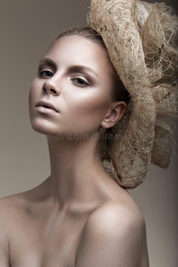 Menina bonita com uma pele de bronze, uma composição pálida e uns acessórios incomuns Imagem da beleza da arte Face da beleza imagens de stock