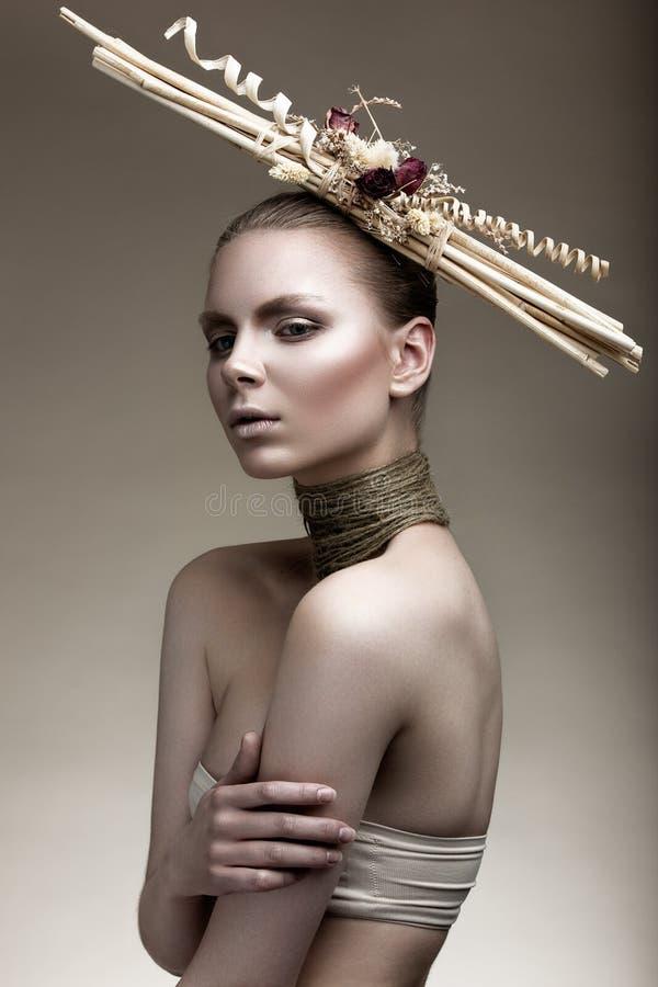 Menina bonita com uma pele de bronze, uma composição pálida e uns acessórios incomuns Imagem da beleza da arte Face da beleza imagens de stock royalty free
